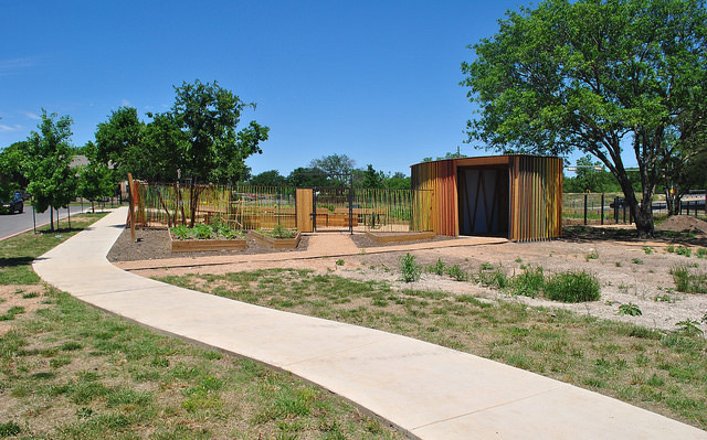 A view of the newly built fence and shed, newly planted trees, and some planters located on the exterior of the North Austin Community Garden. © Art in Public Places Program, 2014.
