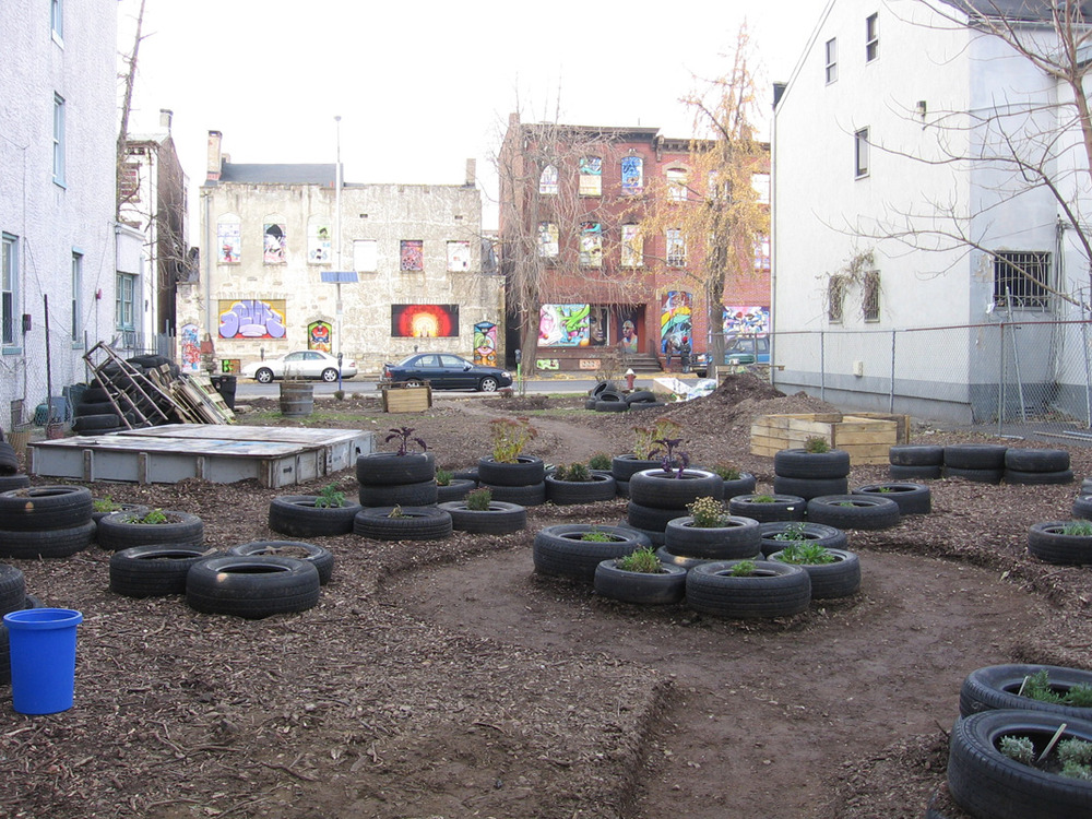 As part of the Gandhi Garden's design, S.A.G.E. Coalition arranged the abandoned tires into planters and dividers that help direct the flow of the walkways.