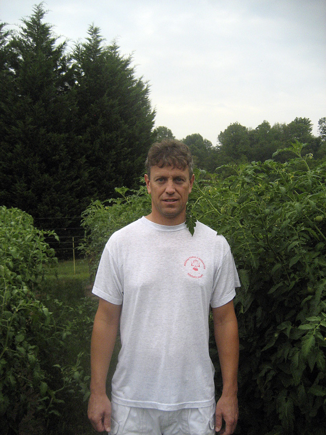 The author in his home garden, with tomato plants in the background, 2009.
