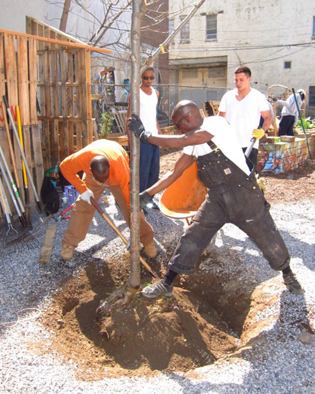 Community members help plant trees during construction of the Gandhi Garden.