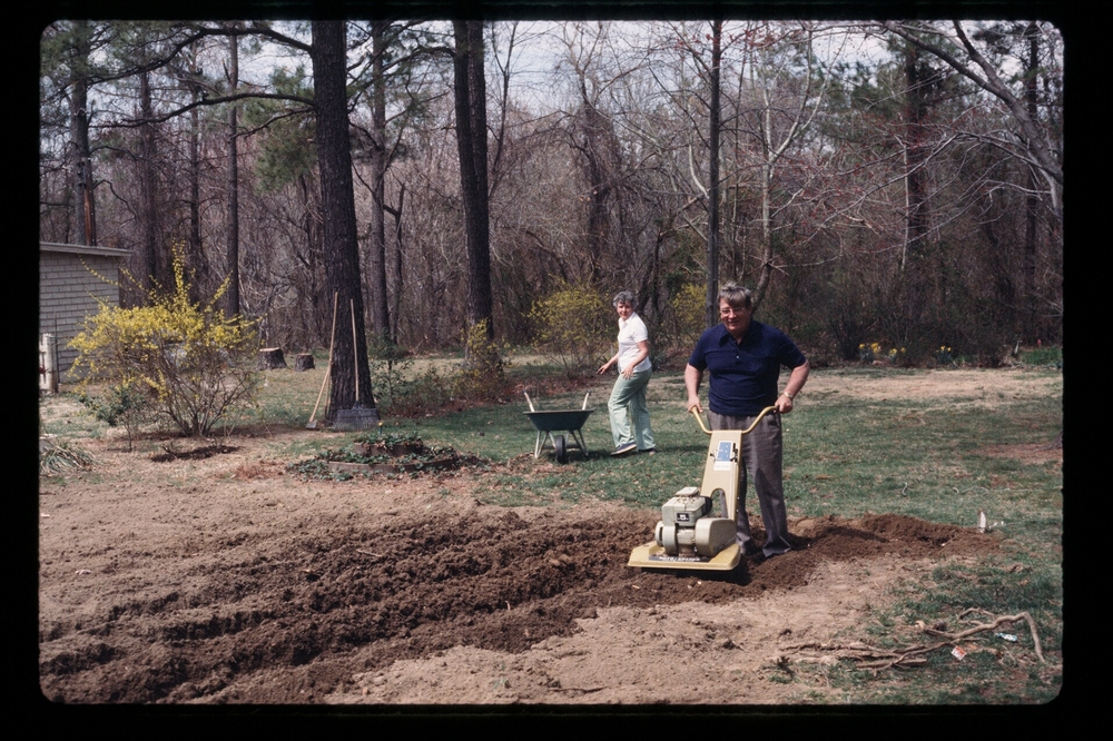 The author's parents, Jack and Ginny, tilling their garden, 1977.