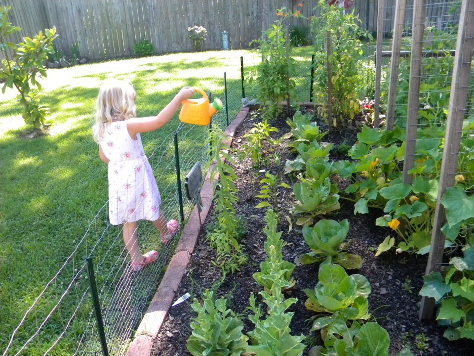 Susan's granddaughter waters the garden.