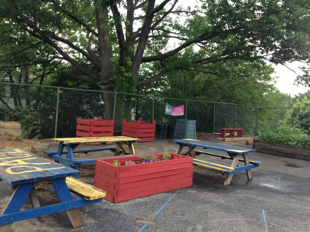 The school garden is located on  a blacktop in a fenced-in area next to the school. This photograph was taken before the students repainted the picnic tables. Spring 2014.