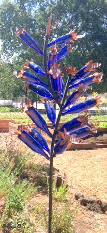 "The Blue Bottle Tree was installed in the garden in July 2014 and designed by artist Suja Pritchard. Pritchard also led the ""Small Worlds Workshop"" at the garden."