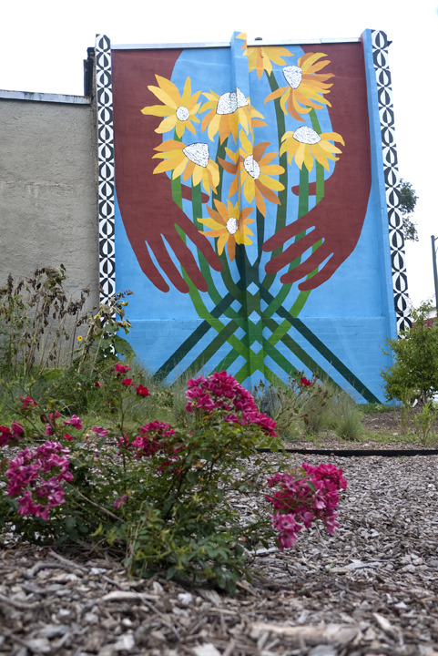 The design on the north wall of the Sunflower Village features a brightly-colored painting of two hands holding a bundle of sunflowers.