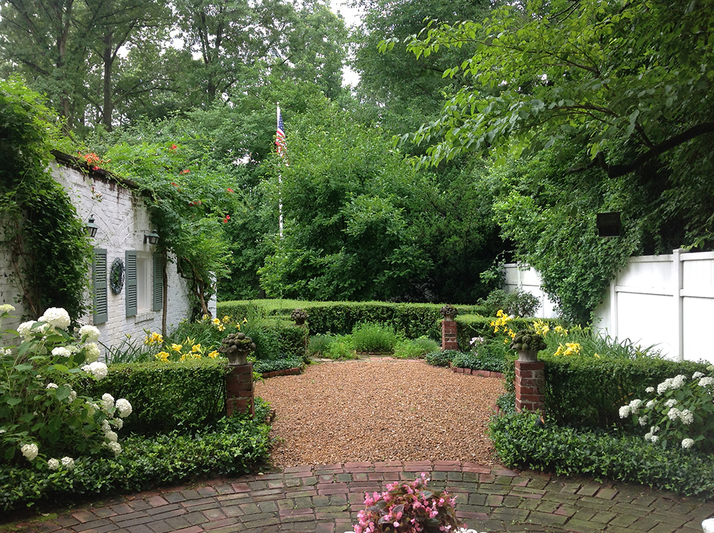 The paved Terrace surrounded by blooming hydrangea transitions to the Day Lily and Herb Gardens