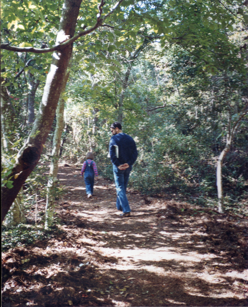 Larry walking with his daughter Kate through the wooded backyard of Hank and Isabel's home in Gaithersburg, Maryland, circa early 1980s.