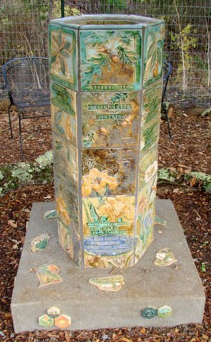 The hexagonal bird bath ornamented with tiles serves to thank donors for their contributions and beautify the garden.
