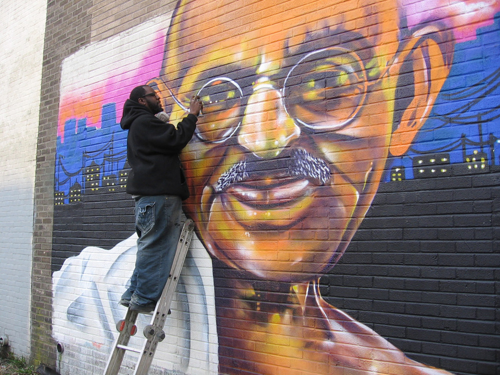 "Will ""Kasso"" Condry paints over the original Gandhi mural with a newer, more vibrant version.&lt;br /&gt;<br />"